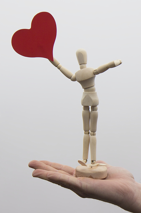 Articulated doll with a red heart over human hand Photograph by Fernando Trabanco Fotografía