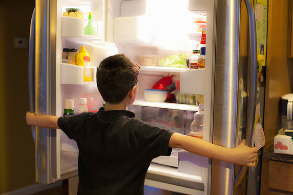 Asian boy searching through refrigerator Photograph by Jed Share/Kaoru Share