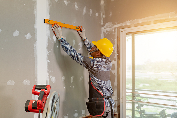 Asian carpenter is working to install interior furniture. Photograph by Sutiporn Somnam