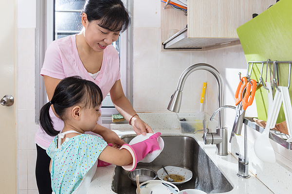 Asian Chinese little girl helping mother washing dishes Photograph by Kiankhoon