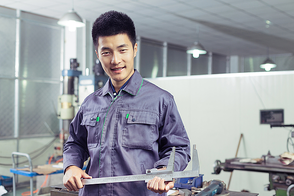 Asian mechanic worker portrait in the workshop of factory Photograph by Loveguli