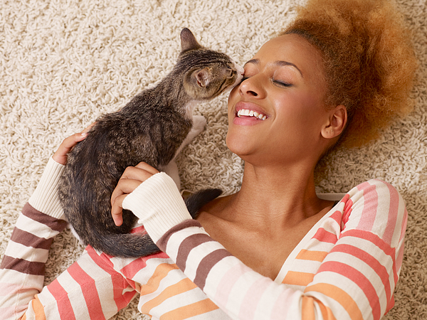 Attractive Young African Woman Laying On Carpet With Cat Photograph by StudioThreeDots