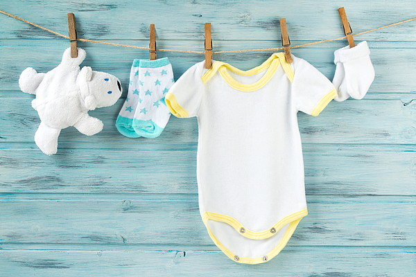 Baby clothes, onesie, socks, white bear toy on a clothesline Photograph by Dash_med