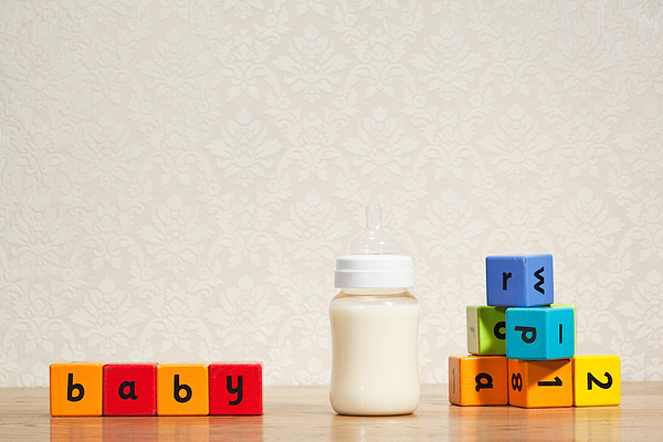 Baby milk and alphabet blocks Photograph by Image Source