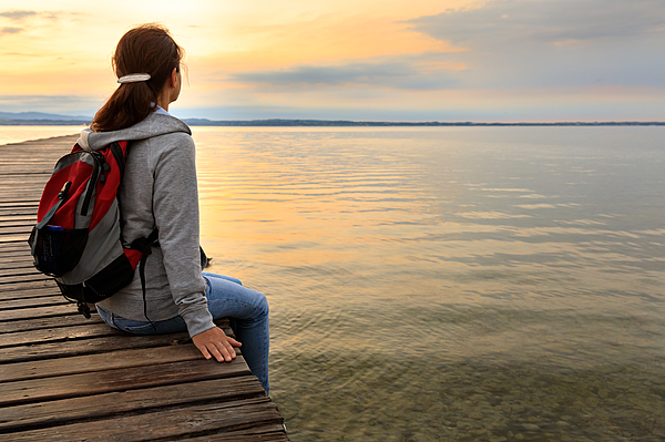 Backpacker on wooden jetty Photograph by FredFroese