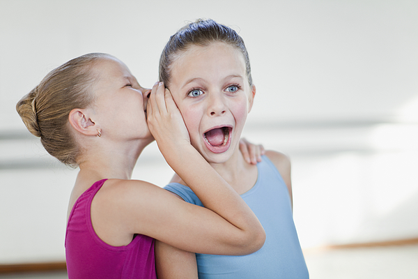 Ballet dancers whispering in studio Photograph by Hybrid Images