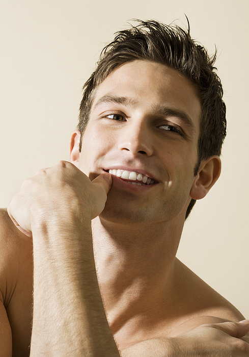Bare chested young man, smiling, portrait  Photograph by Pando Hall
