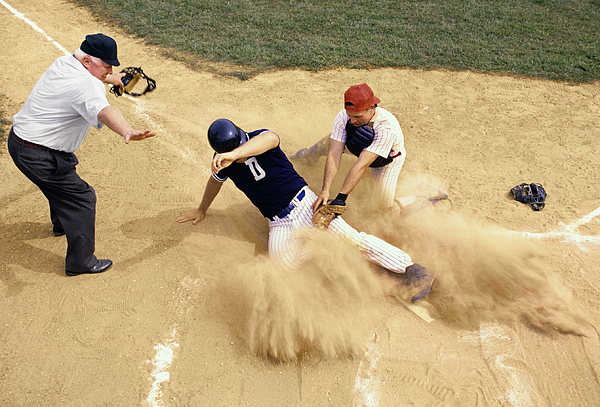 Baseball player sliding into home plate Photograph by Jupiterimages