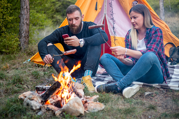 Beautiful Couple, Sitting, Camping Around The Campfire. On The Background With A Tent The Man Flicks The Fire With A Stick. Photograph by MajaMitrovic