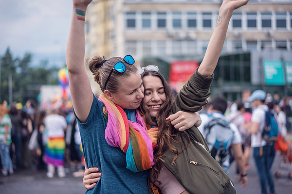 Beautiful female couple hugging while marching on the street Photograph by Mixmike