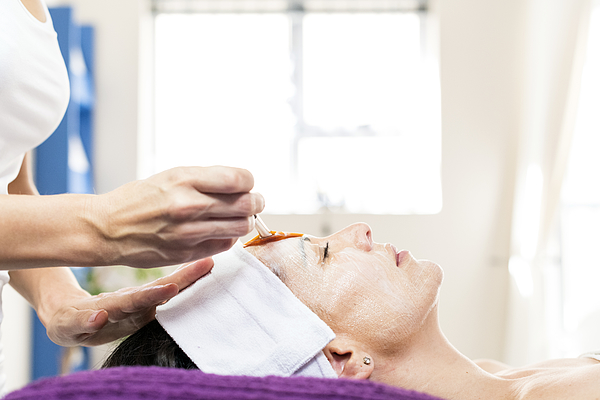 Beauty Therapist Applying A Face Mask To A Client Photograph by PixelCatchers