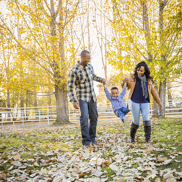 Black family playing in autumn leaves Photograph by Mike Kemp