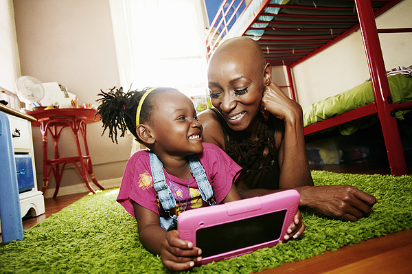 Black mother and daughter using digital tablet in bedroom Photograph by Peathegee Inc