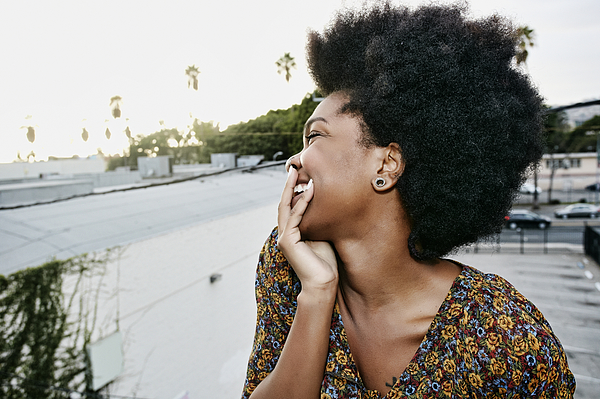 Black woman smiling on urban rooftop Photograph by Peter Griffith