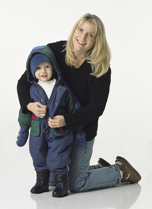 Blonde Mom Kneels Behind Young Son Putting His Coat On With A Smile Photograph by Photodisc