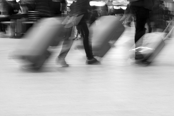 Blurred movement of Travellers with luggage Photograph by Lyn Holly Coorg