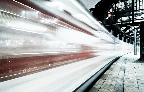 Blurred train at night leaving station Photograph by Bernd Schunack