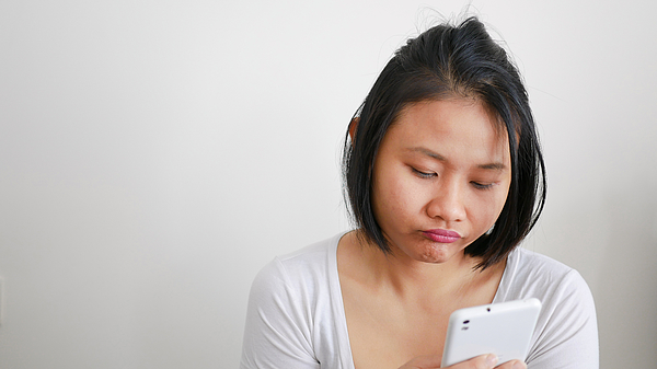 Bored Young Woman Using Phone Against White Wall Photograph by Sanyalux Srisurin / EyeEm