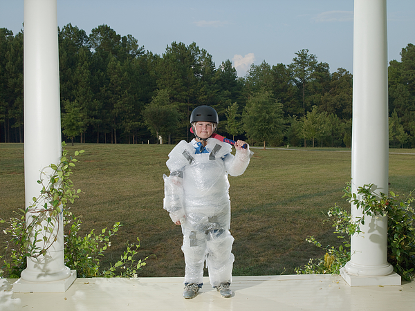 Boy (10-11) wrapped in bubble wrap, standing on porch with baseball bat Photograph by D. Anschutz