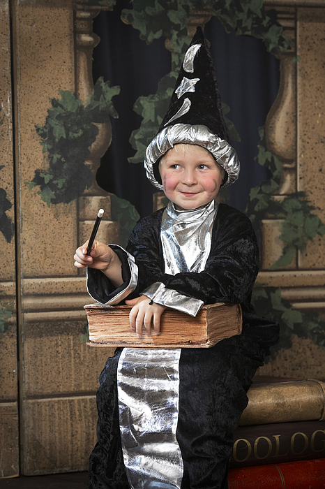 Boy (3-5) on stage in wizard costume, looking away, smiling Photograph by Richard Lewisohn