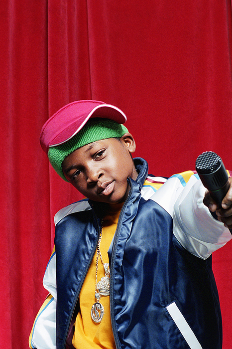 Boy (9-11) holding out microphone, close-up Photograph by Digital Vision