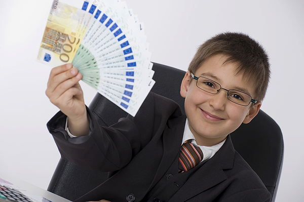 Boy dressed as a businessman holding a fan of banknotes Photograph by Michaela Begsteiger