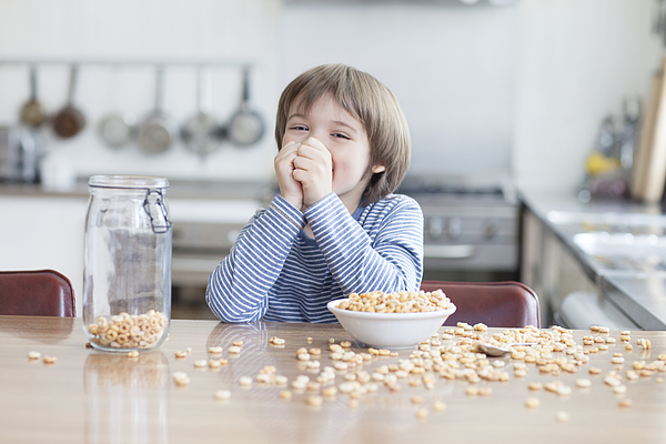 Boy eating bowl of cereal in kitchen Photograph by Compassionate Eye Foundation/Natasha Alipour Faridani