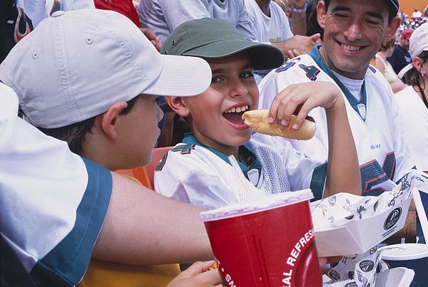 Boy Eating Hot Dog in Stadium Photograph by Juan Silva