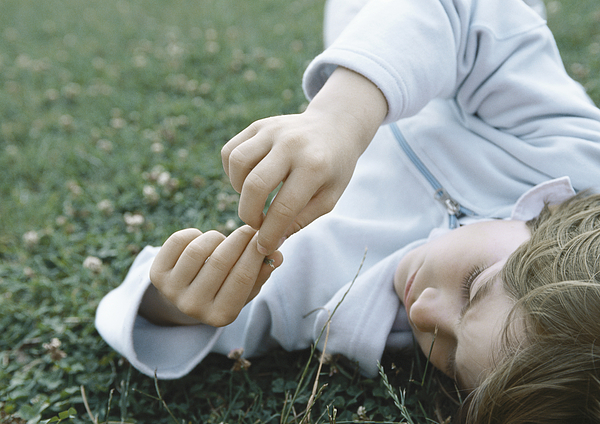 Boy Lying On Grass Holding Fingers Together In Front Of Face Photograph by Laurence Mouton