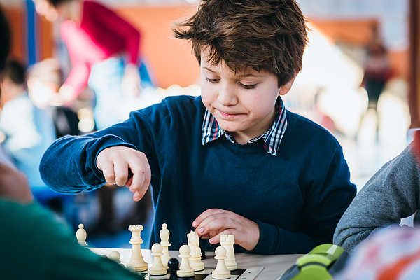 Boy playing in a chess school championship Photograph by Click&Boo