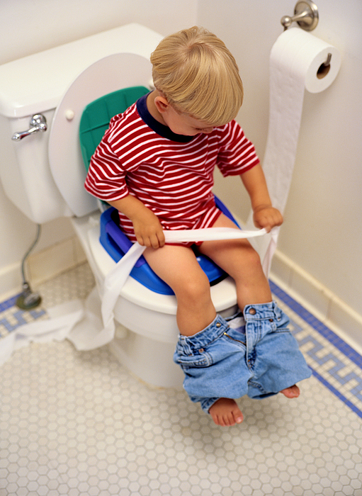 Boy Sitting on a Potty Chair With Toilet Paper Photograph by Ryan McVay