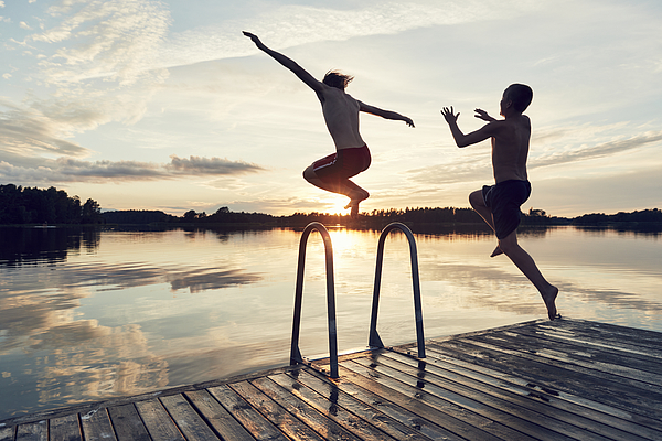 Boys jumping into lake Photograph by Johner Images