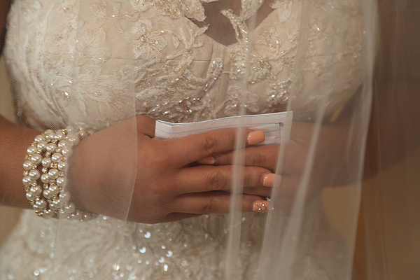Bride holding written vows, hands clasped Photograph by Holly Harris