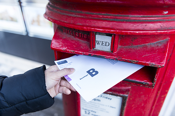 British Postal voting envelop is being dropping into a postbox Photograph by Sunphol Sorakul
