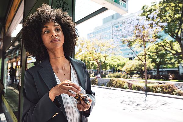 Business afro american woman at bus stop in downtown Photograph by LeoPatrizi