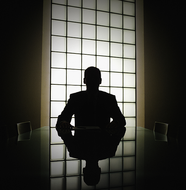 Business man or boss in silhouette interview Photograph by John Rensten
