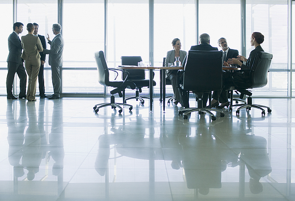 Business people meeting in separate groups in conference room Photograph by Martin Barraud