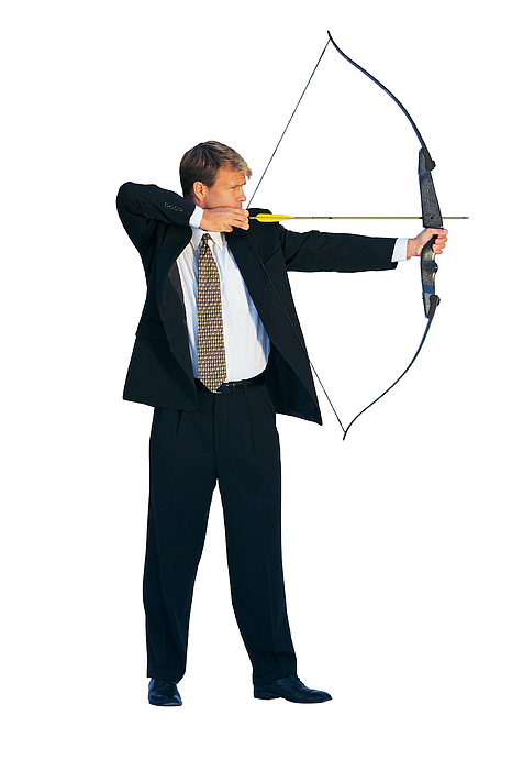 Businessman aiming bow and arrow Photograph by Comstock