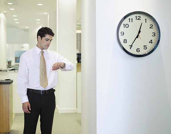 Businessman checking watch in office by clock Photograph by Robert Daly