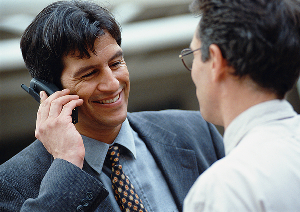Businessman Holding Cell Phone, Smiling Photograph by Eric Audras