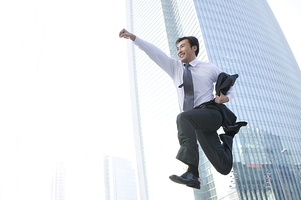 Businessman jumping in front of tall building Photograph by Lane Oatey