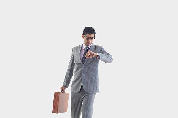 Businessman looking at watch Photograph by Abhinandita Mathur