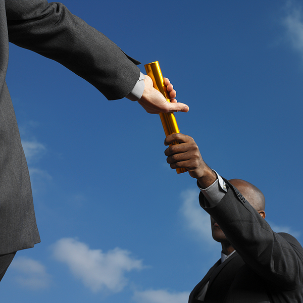 Businessman Passing Baton To Businessman, Low Angle View Photograph by George Doyle