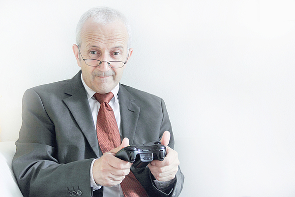 Businessman playing video games Photograph by Sigrid Gombert