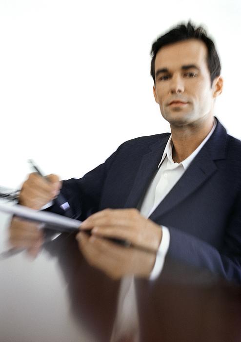 Businessman Sitting At Desk, Blurred, Portrait Photograph by Vincent Hazat