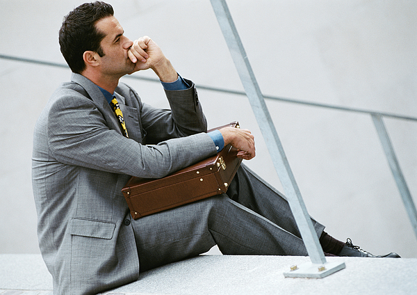 Businessman sitting on stairs, holding briefcase Photograph by Eric Audras
