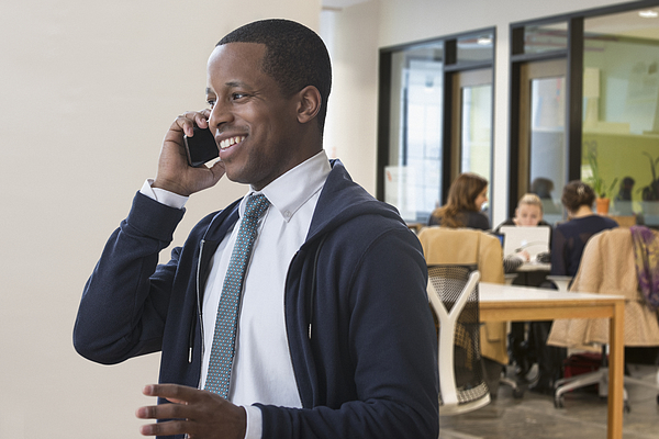 Businessman talking on cell phone in office Photograph by Jose Luis Pelaez Inc