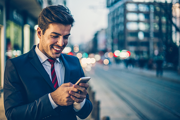 Businessman texting outdoors in the evening Photograph by Pixelfit