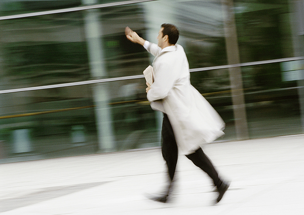 Businessman Walking In Street, Hand Raised, Blurred Photograph by Eric Audras