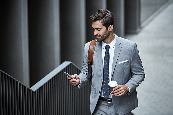 Businessman with cup and mobile phone on stairs Photograph by Morsa Images